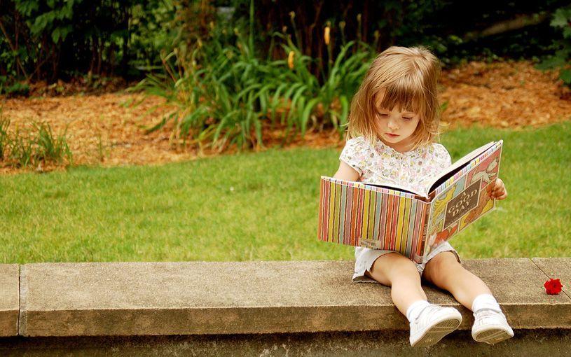 Ребенок сидит и читает книгу